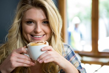 Smiling young woman having coffee in cafe