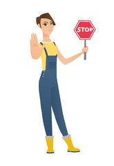 Caucasian farmer holding stop road sign.