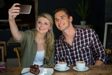 Smiling couple taking selfie with cell phone in cafeteria