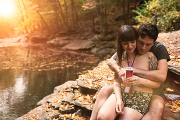 Young couple sitting near a stream