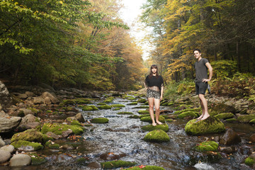 Young couple standing in a mossy stream
