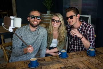 Happy friends taking selfie with monopod in coffee shop
