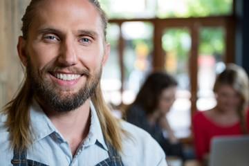 Portrait of confident male barista in coffee shop