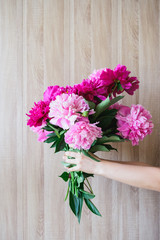 white caucasian woman holding red and pink peonies bouquet at wood wall backdrop