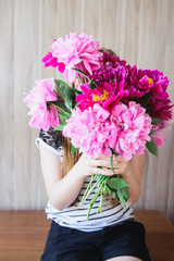 happy white caucasian girl holding red and pink peonies bouquet in front of face at wood wall backdrop