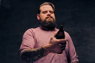 Fat bearded hipster male with tattoos on arms holds beer bottle.