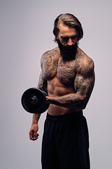 A man with long hair and tattoo on his torso holds dumbbell.