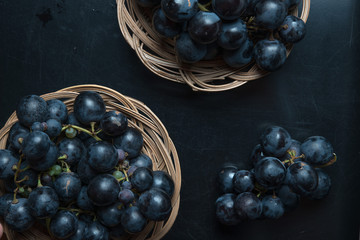 Black grape on rustic wicker plate
