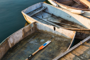 Close Up of Three Old Wooden Row Boats tied to a Pier