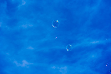blowing bubbles into blue sky