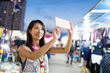 Woman taking photo in night market