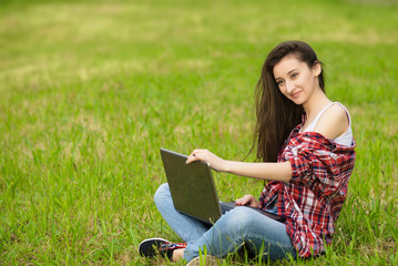 Pretty woman with computer note-book sitting on the grass in the park