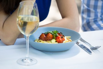 Cropped image of couple with food and wineglass on table