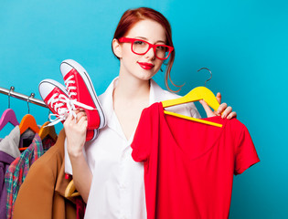 photo of beautiful young woman with shirt on hanger and gumshoes near clothes on the wonderful blue background