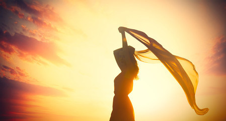 photo of beautiful young woman with shawl on the wonderful sunset background