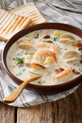 American food: New England clam chowder soup close-up on a in a bowl. vertical