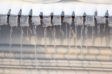 Icicles on the roof of the house at sunset