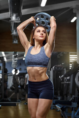 Girl sporting with dumbbells  hand in gym.
