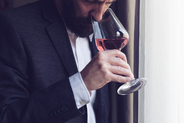 man tasting a glass of rose wine