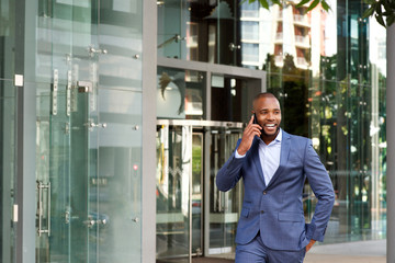 happy young african american businessman talking on cell phone