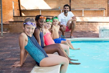 Happy male instructor and children relaxing at poolside