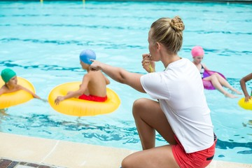 Lifeguard whistling while instructing children in swimming pool
