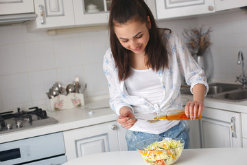 young beautiful woman cooking salad on the kitchen. pretty girl eating healthy organic fresh vegetables.