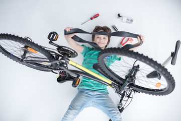 top view of smiling boy holding tire while lying under bicycle