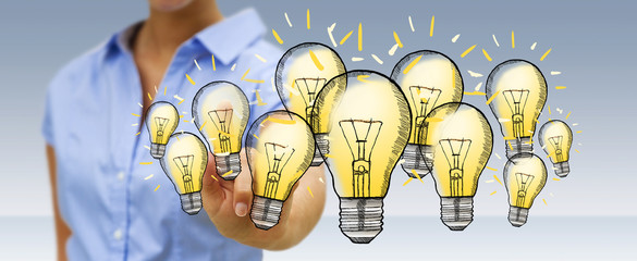 Businesswoman touching hand-drawn lightbulb with her finger