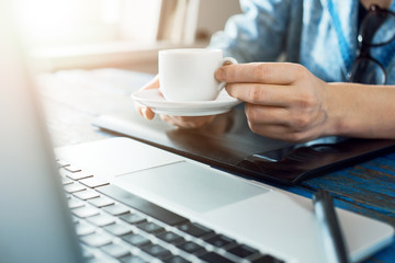 Person holding a coffee cup while working on the laptop