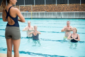 Mid section of yoga trainer assisting senior swimmers