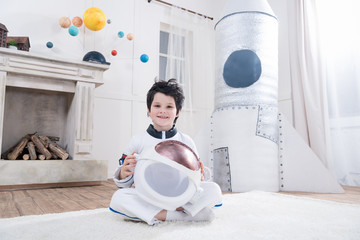 boy in astronaut costume holding helmet, toy rocket behind