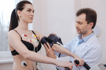 Competent modern doctor using special tools for measuring blood pressure