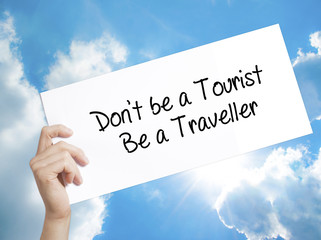Don't be a Tourist Be a Traveller  Sign on white paper. Man Hand Holding Paper with text. Isolated on sky background