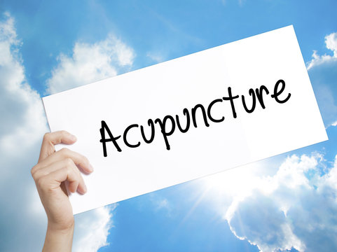 Acupuncture Sign on white paper. Man Hand Holding Paper with text. Isolated on sky background.