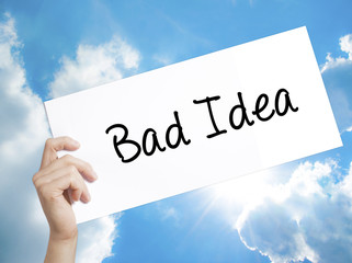 Bad Idea Sign on white paper. Man Hand Holding Paper with text. Isolated on sky background.