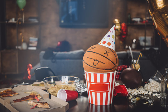 Close-up view of basketball ball with funny face in popcorn box and messy table after party