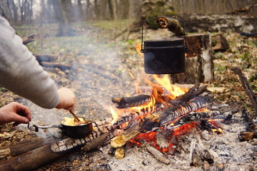 Preparing food on campfire in wild camping as