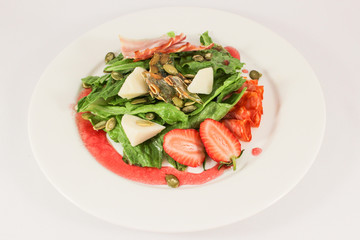 Mix of hot sausages with bacon on a cushion of lettuce leaves, in a duet with parmesan and strawberries, garnished with pumpkin seeds, dressed with raspberry sauce