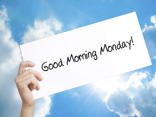 Good Morning Monday! Sign on white paper. Man Hand Holding Paper with text. Isolated on sky background