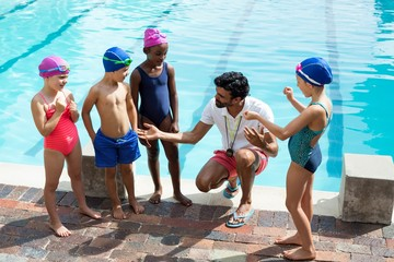 Male trainer assisting children at poolside