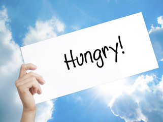 Hungry! Sign on white paper. Man Hand Holding Paper with text. Isolated on sky background