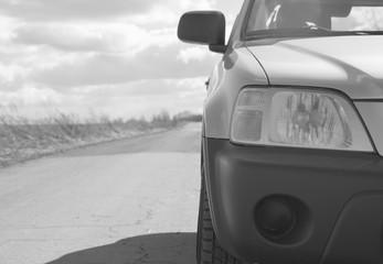 black and white, closeup of headlight SUV car on the asphalt road.