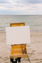 Easel with an empty canvas for drawing the sea