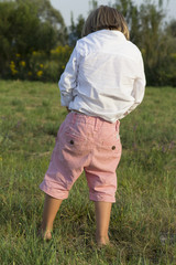 Young blonde boy peeing outdoors on green grass, on sunny summer afternoon