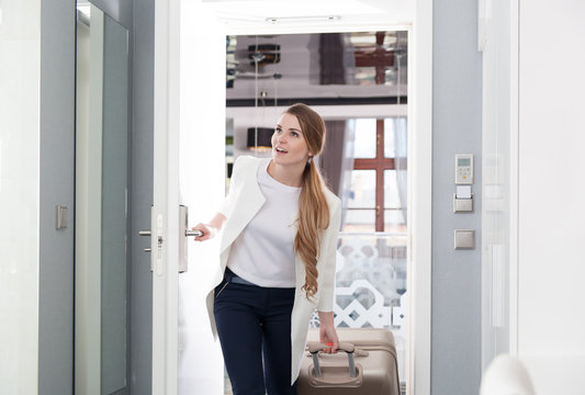Delighted woman with suitcase opening door at modern hotel room