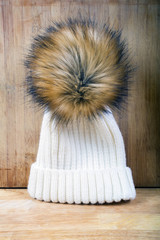 Women's knitted white hat with fur pompon