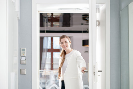 Delighted woman opening door at modern hotel room