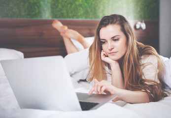 Pretty woman on bed in modern apartment using laptop after wake up