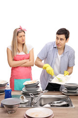 Angry woman making her husband do the dishes